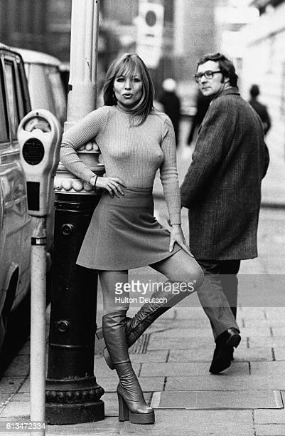 Susan Shaw turns the heads of passersby as she models a miniskirt ribbed turtleneck sweater and platformheeled boots in a street UK 1975