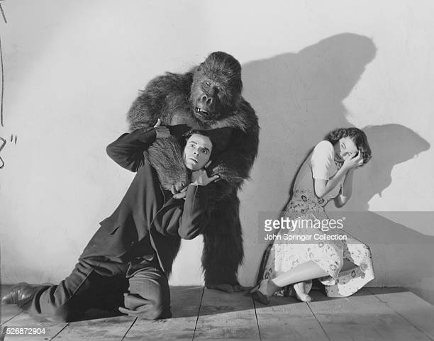 Susan Webster cowers in horror as a gorilla monster chokes a man in the 1941 scifi horror film The Monster and the Girl