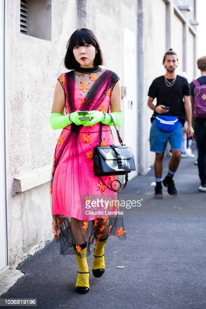 Susanna Lau wearing a neon fuchsia dress is seen in the streets of Milano before the Prada show during Milan Fashion Week Spring/Summer 2019 on...