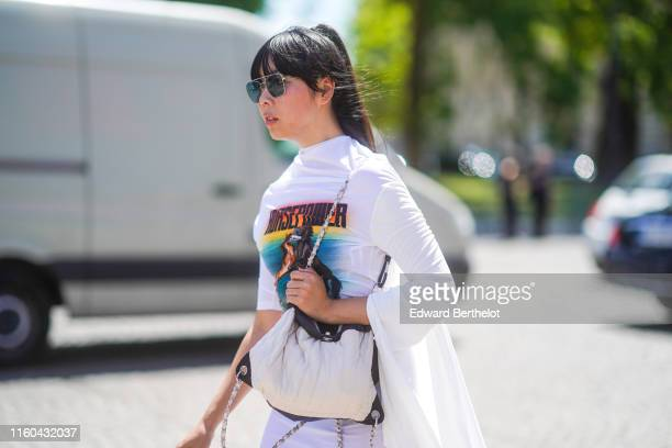 Susanna Lau wears sunglasses a white Chanel bag a white flowing dress with colored patch outside Chanel during Paris Fashion Week Haute Couture...