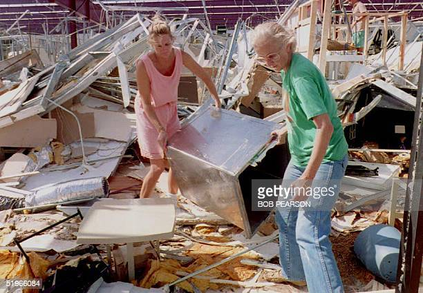 Susanne Miller and Cheryl Winchester of Homestead clear the rubble from their pet supply store in Homestead, Florida 25 August 1992 as Floridians...