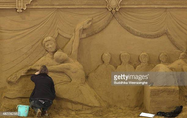 Susanne Ruseler of Holand finishes a sand sculpture named 'Russian musical cultureTchaikovsky and ballet dancers' at the Sand Museum in the Tottori...
