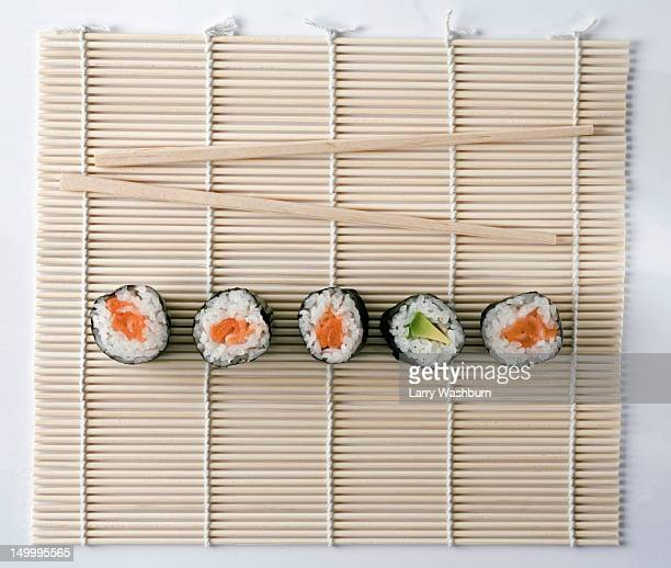 sushi and chopsticks on a wooden mat - maki sushi stock pictures, royalty-free photos & images