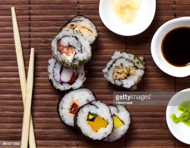 sushi and chopsticks on a wooden mat - soy sauce stock photos and pictures