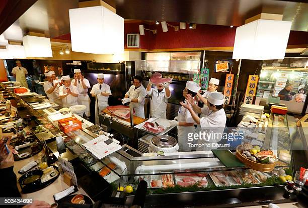 A sushi chef center right holds a section of tuna at a Sushi Zanmai sushi restaurant operated by Kiyomura KK after the year's first auction at...