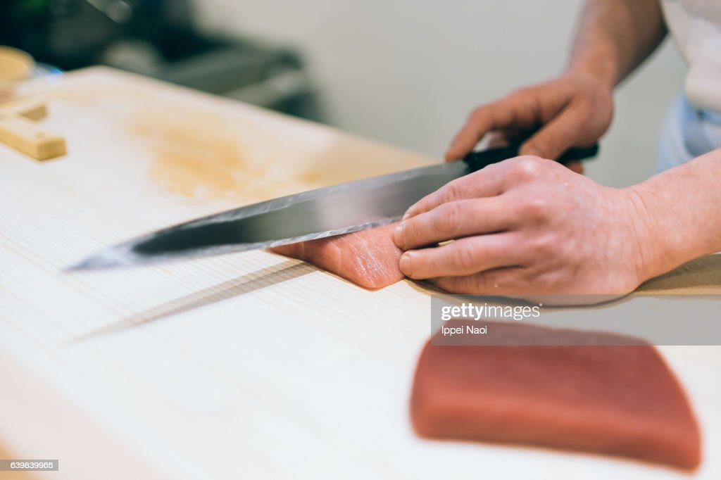 Sushi chef cutting fresh Japanese bluefin tuna at bar, Tsukiji : Stock Photo