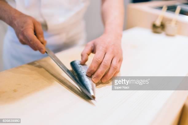 Sushi chef cutting fresh Japanese sardine at bar, Tsukiji