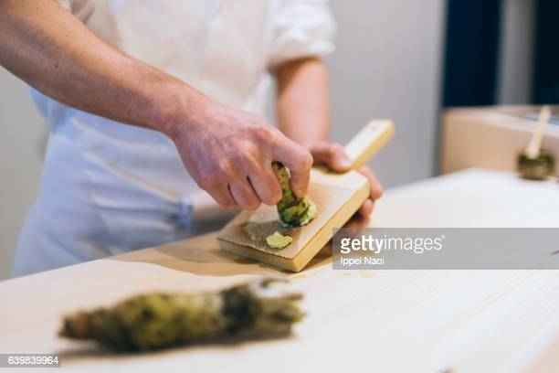 Sushi chef grating fresh wasabi at sushi bar