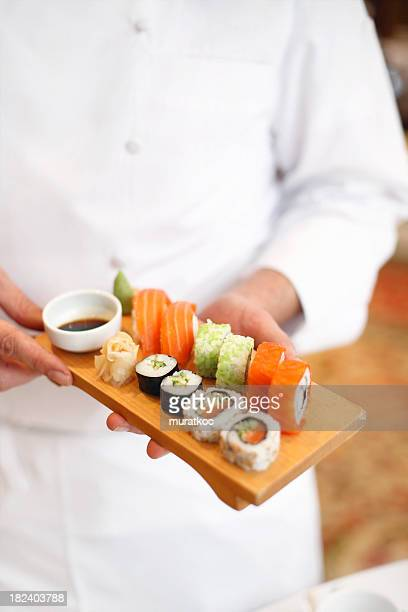 Sushi chef holding a tray of fresh sushi on a wood plater