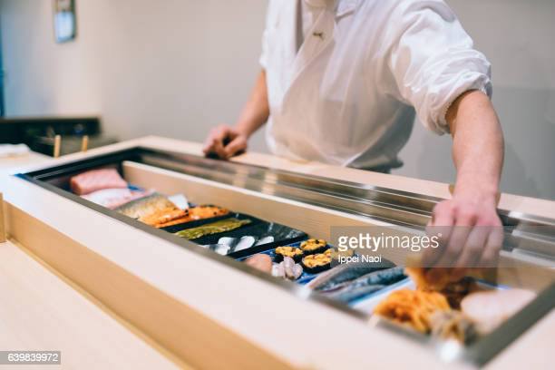 sushi chef picking up fresh seafood for nigiri zushi at bar, tsukiji - sushi restaurant stock photos and pictures