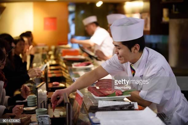A sushi chef serves a piece of sushi at a Sushi Zanmai sushi restaurant in Tokyo Japan on Friday Jan 5 2018 Kiyomura KK operator of Sushi Zanmai...