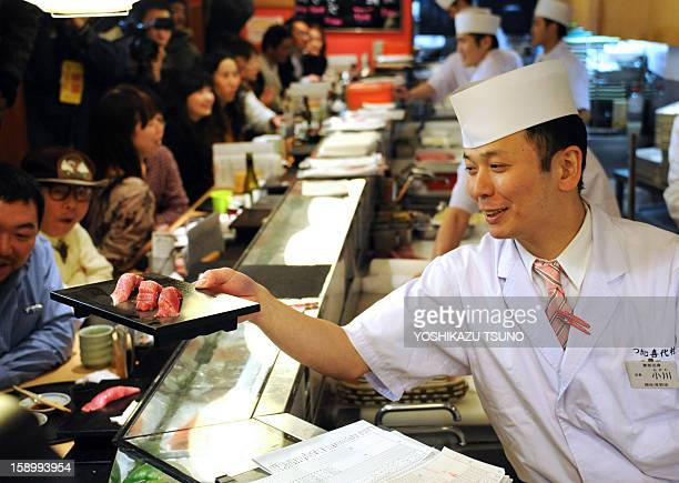 A sushi chef serves up tuna sushi made from a 222kg bluefin tuna purchased earlier in the day for a record price and sliced up for customers at the...