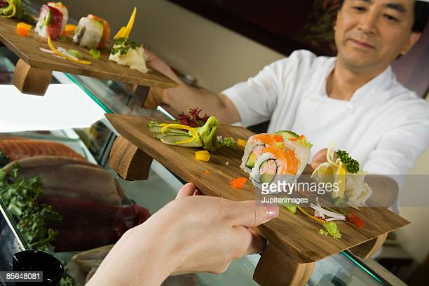 sushi chef serving sushi - wasabi sauce stock pictures, royalty-free photos & images