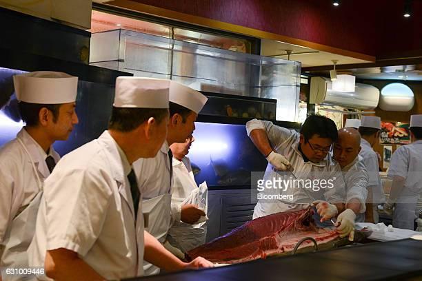Sushi chefs cut a tuna at a Sushi Zanmai restaurant in Tokyo Japan on Thursday Jan 5 2017 Kiyomura KK operator of Sushi Zanmai restaurant made the...