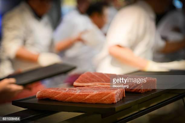 Sushi chefs prepare plates of tuna sushi at a Sushi Zanmai restaurant in Tokyo Japan on Thursday Jan 5 2017 Kiyomura KK operator of Sushi Zanmai...