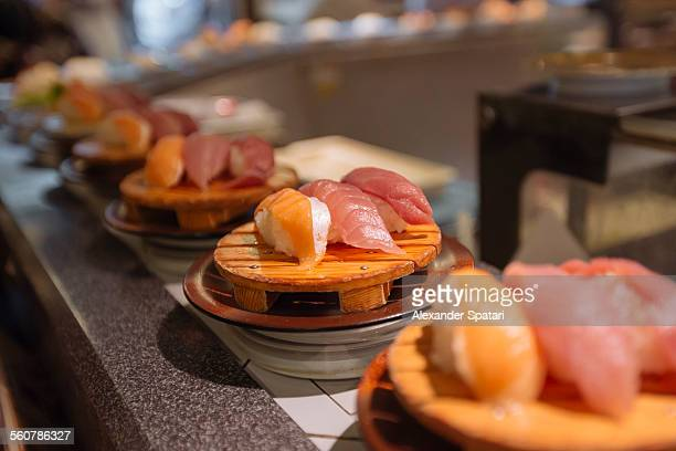 sushi on conveyor belt - sushi restaurant stock photos and pictures