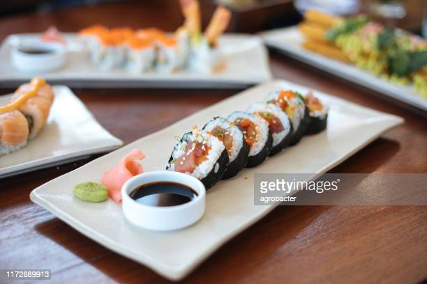 sushi plates on table - nori stock pictures, royalty-free photos & images