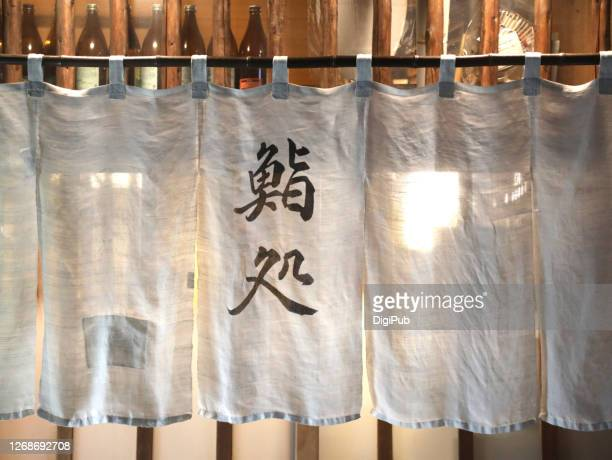 sushi restaurant noren curtain in the night - のれん ストックフォトと画像