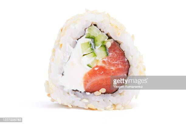 sushi roll with salmon and avocado in sesame seeds - maki sushi stock pictures, royalty-free photos & images