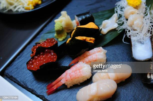 Sushi rolls and nigiri on black stone slate