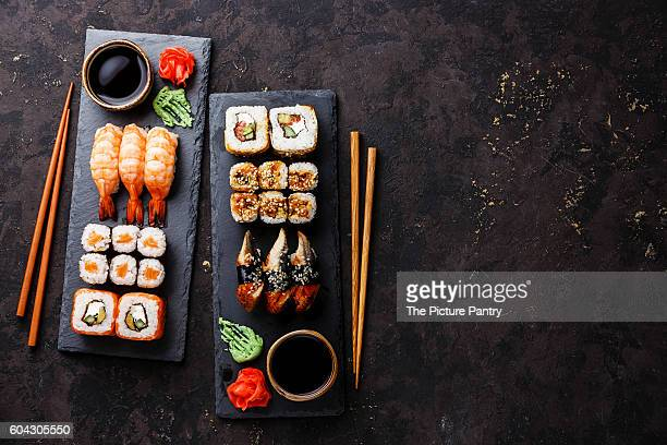 Sushi rolls, maki, nigiri Set served for two on black stone slate on dark background