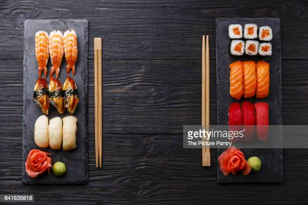 sushi rolls, maki, nigiri set served for two on black stone slate on dark wooden background - wasabi sauce stock pictures, royalty-free photos & images
