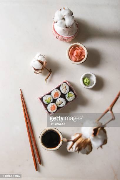 Sushi rolls set in pink ceramic serving plate with chopsticks bowls of soy sauce and pickled ginger cotton flowers over white marble background Flat...