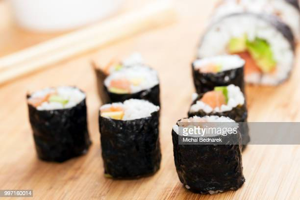 sushi rolls with salmon, avocado, rice in seaweed and chopsticks - nori stock photos and pictures