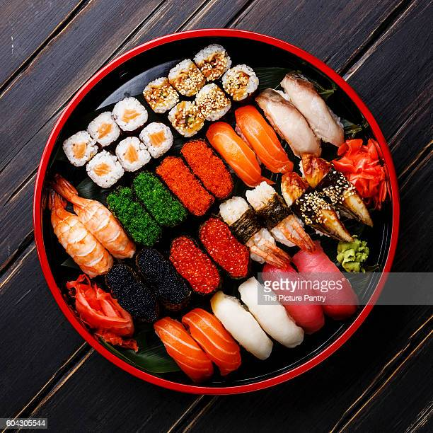 Sushi Set gunkan, nigiri and rolls served in traditional Japan black Sushioke round plate