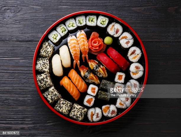 sushi set nigiri and rolls served in traditional japan black sushioke round plate - maki sushi stock pictures, royalty-free photos & images