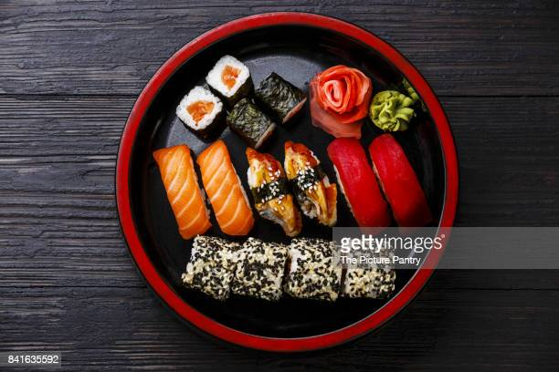 sushi set nigiri and rolls served in traditional japan black sushioke round plate on burned black wooden background - wasabi sauce stock pictures, royalty-free photos & images