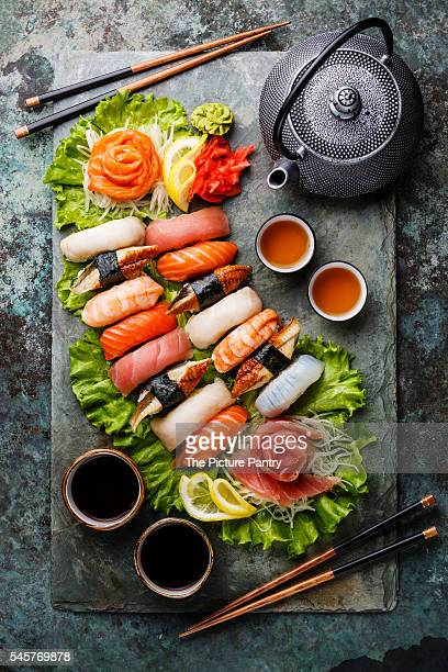 sushi set nigiri and sashimi with tea served on gray stone slate on metal background - nigiri stock pictures, royalty-free photos & images