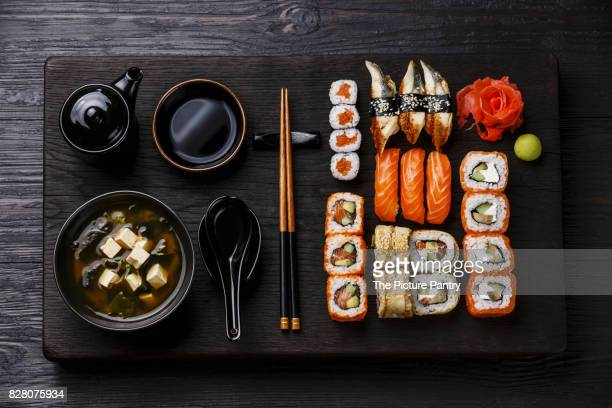 Sushi Set nigiri and sushi rolls and Miso Soup with tofu on wooden serving board block on black background