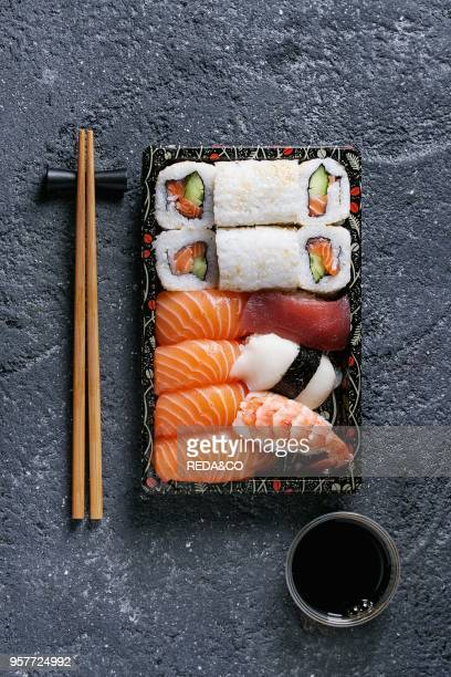 Sushi Set nigiri and sushi rolls in plastic food delivery box with soy sauce and chopsticks over black stone texture background Top view with space...