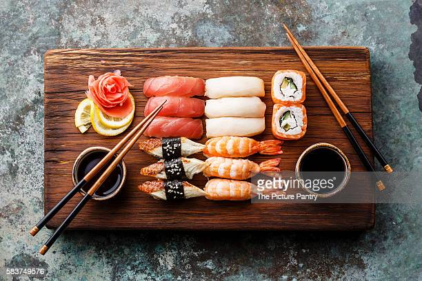 Sushi Set nigiri and sushi rolls served for two on wooden serving board block