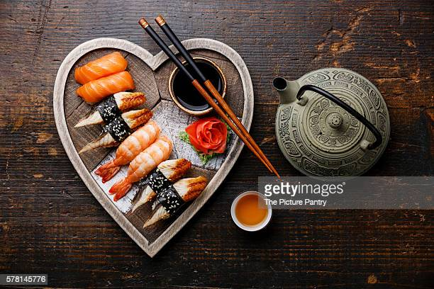 Sushi Set nigiri and tea served on Heart shape wooden tray on dark wooden background