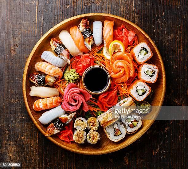 sushi set nigiri, rolls and sashimi served in wooden round tray - sashimi fotografías e imágenes de stock
