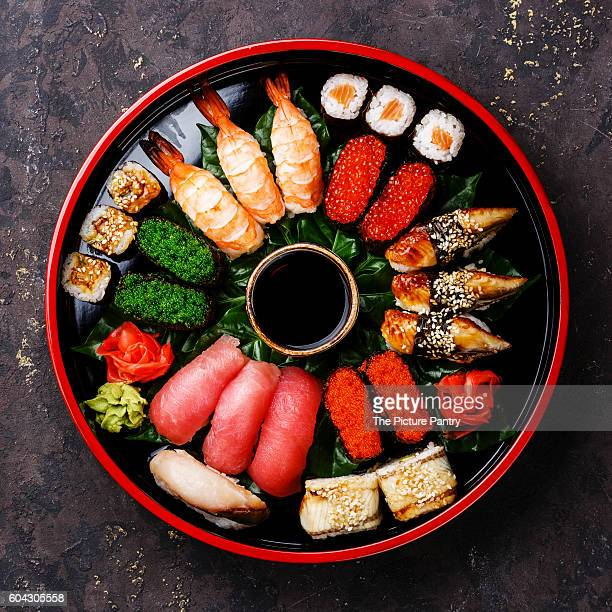 sushi set nigiri, rolls, gunkan and sashimi served in traditional japan black sushioke round plate - soy sauce stock photos and pictures