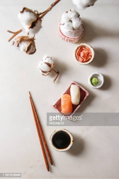 Sushi Set nigiri with salmon and butterfish in pink ceramic serving plate chopsticks bowls of soy sauce and pickled ginger cotton flowers over white...