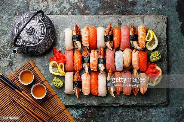 Sushi Set nigiri with tea served on gray stone slate on metal background