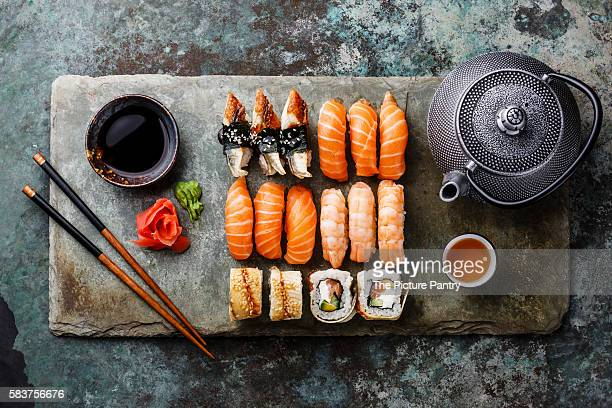 Sushi Set with tea served on gray stone slate on metal background