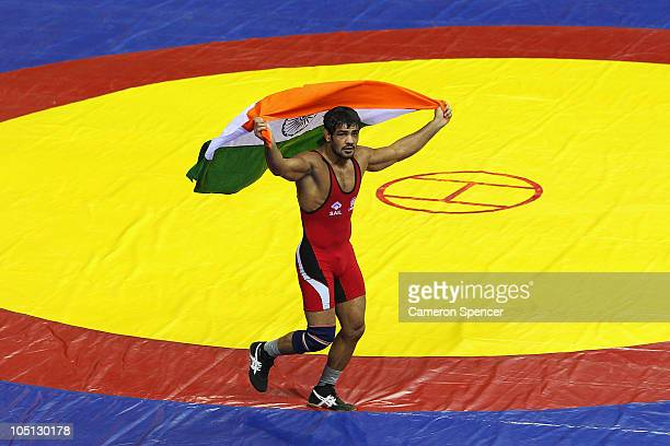 Sushil Kumar of India runs a lap of honour after winning against Heinrich Barnes of South Africa in the men's 66kg freestyle gold medal wrestling at...