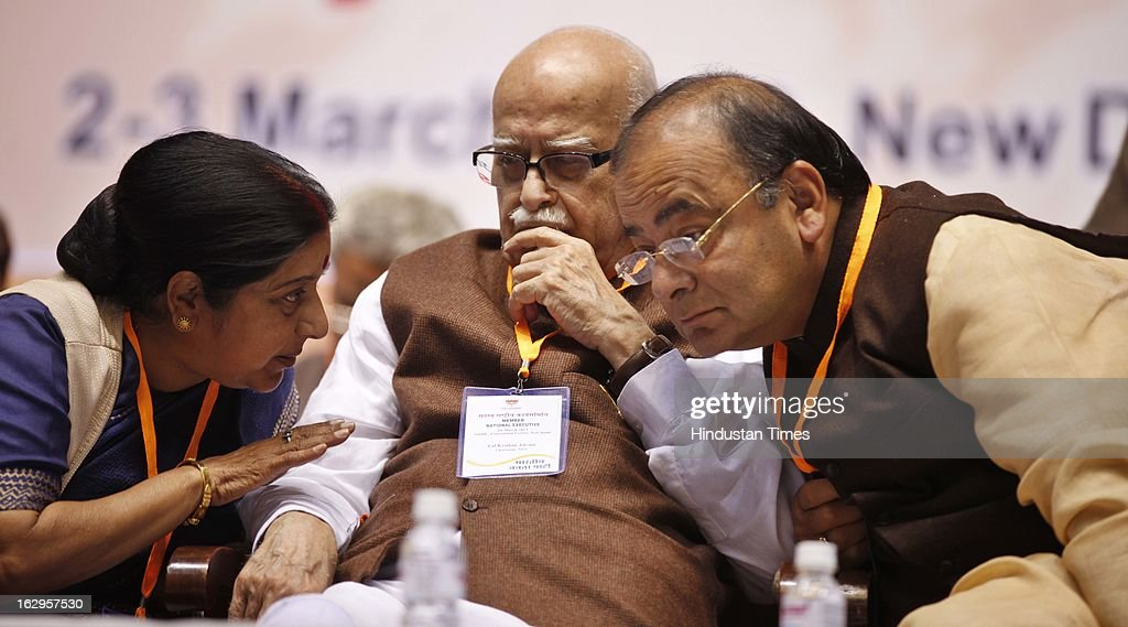 Sushma Swaraj talking with Senior party leaders L K Advani and Arun Jaitley during Bharatiya Janata Party National Council meeting at Talkatora Indoor Stadium on March 2, 2013 in New Delhi, India. In his 90 minute presidential address Rajnath Singh asked the party ranks to be prepared for early Lok Sabha polls and crucial assembly elections this year, including in Karnataka, Madhya Pradesh, Chhattisgarh, Rajasthan and Delhi all very important states for BJP.