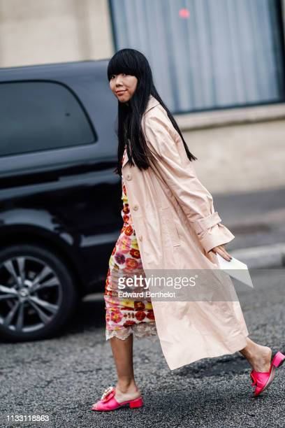 Susie Lau wears a beige trench coat, neon pink mules, a colorful floral print gathered dress, outside Nina Ricci, during Paris Fashion Week...