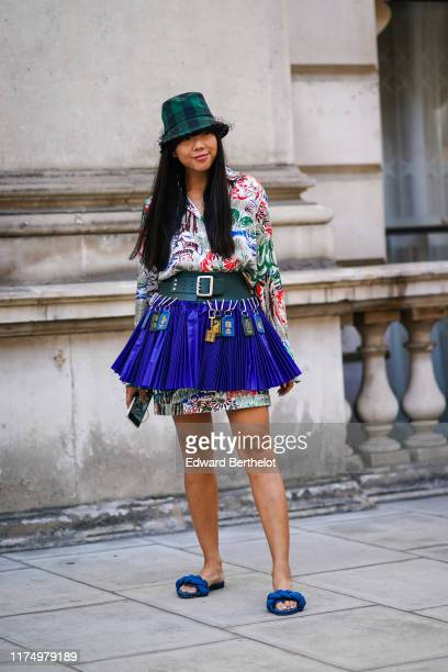 Susie Lau wears a green checked hat a floral print colored shirt dress a green leather large belt with several attachments blue pleated small skirt...