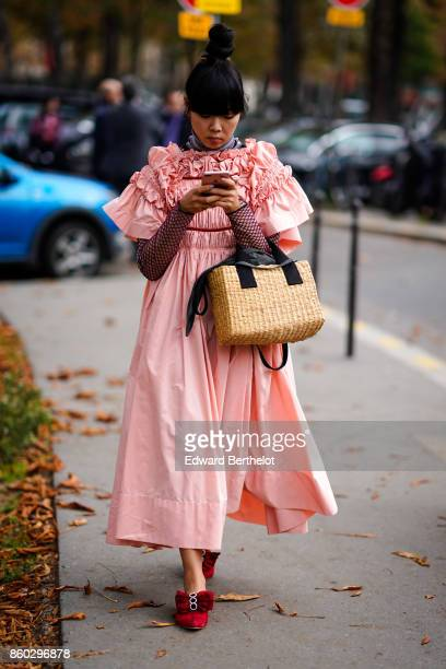 Susie Lau wears a pink gathered skirt a turtleneck top with fishnet sleeves a straw bag red suede shoes with a burgundy bow outside Lanvin during...