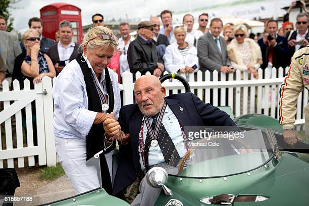 Susie Moss lends a helping hand to Sir Stirling Moss to climb out of the Aston Martin DB3S owned by Steve Boultbee Brooks in the Assembly Area at...
