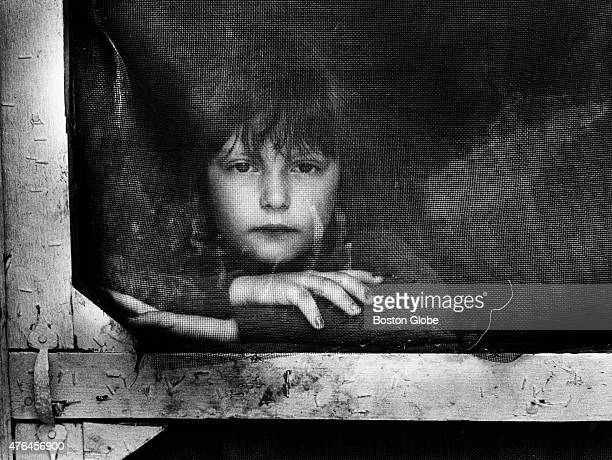 Susie Perkins looks out the window at the converted camp that is home to her parents and two other siblings in Errol NH 1990