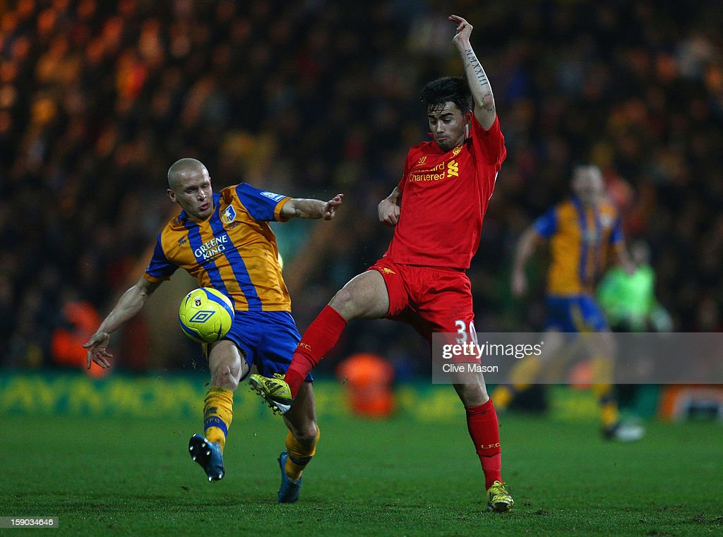 Suso of Liverpool is challenged by Lindon Meikle of Mansfield Town during the FA Cup with Budweiser Third Round match between Mansfield Town and Liverpool at One Call Stadium on January 6, 2013 in Mansfield, England.