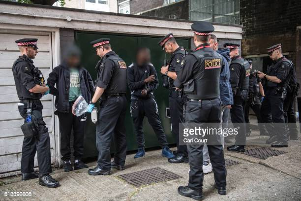 Suspect are detained and searched by police officers after being arrested for alleged possession of a dangerous weapon near Elephant and Castle...